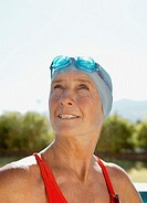 Mature woman wearing swimming cap and goggles outdoors