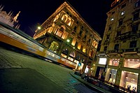 Italy, Milan, tram travelling on city street, night (blurred motion)