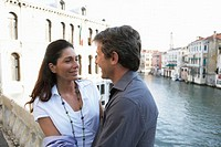 Italy, Venice, couple on canal bridge, smiling at each other
