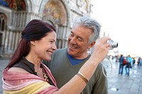 Italy, Venice, mature couple taking photograph in square, smiling
