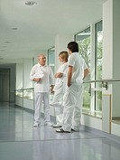 Male doctor talking to male and female nurses in hospital corridor