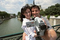 France, Paris, couple on bridge near Notre-Dame, man using camcorder
