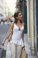 France, Paris, young woman in street, carrying shopping bags