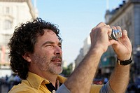 Mature man taking photograph in street, close-up (focus on man)