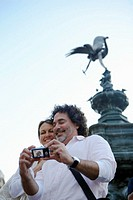 England, London, Piccadilly Circus, couple using camera, smiling