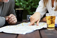 Mature couple sitting at pub table, woman pointing to map, close-up