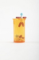 Pill figure climbing out of bottle