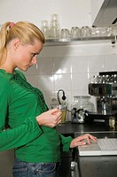 Young woman standing in kitchen using laptop on counter, holding drink
