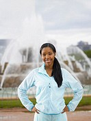 Young woman wearing track suit in front of fountain