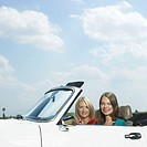 Two women in convertible car, smiling, portrait