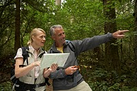 Mature man and woman looking at topographical map, man pointing