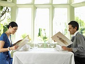 Couple looking at menus at table in restaurant, side view
