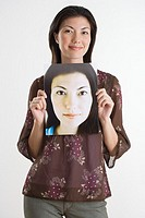 Woman Holding Photograph of Herself