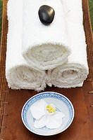 Rolled bath towels and orchid in bowl