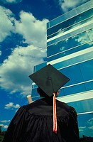 View from behind a college graduate wearing his cap and gown as he looks forward to a career in the business world. He is looking up at the exterior o...
