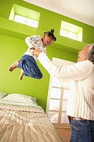 Grandmother Helping Girl Jump on Bed