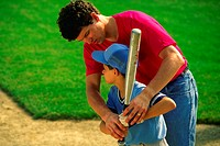 Dad/coach helps little leaguer work on batting abilities.MR