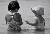 Two young sisters sitting in the water at the beach playing together.