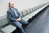 Businessman Sitting in Row of Chairs