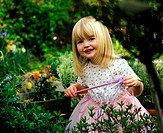 A blonde three year old girl wearing a fairy costume and holding a magic wand stands in a garden.