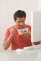Man sitting by computer eating food