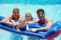 Portrait of parents with their two daughters on a pool raft in a swimming pool