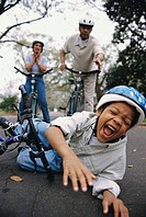 Close-up of a boy fallen off of a bicycle with his grandparents standing behind him