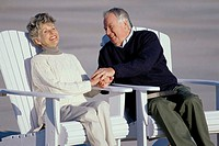 Senior couple sitting in adirondack chairs