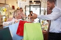 Store Clerk Handing Woman Shopping Bags