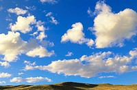 Cumulus Clouds Floating Above Prairie in the Fall
