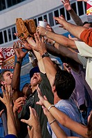 Low angle view of a group of men reaching out for a baseball glove