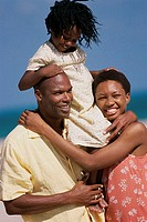 Close-up of a daughter riding on her father´s shoulders on the beach with her mother standing beside them