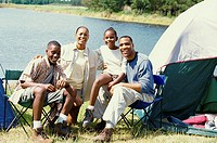 Portrait of parents sitting at a campsite with their son and daughter