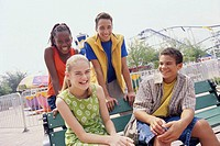 Two teenage couples sitting in an amusement park and smiling