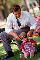 Father putting sunglasses on his son