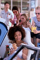 High angle view of a young woman eating food with her friends in a car