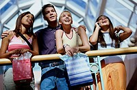 Low angle view of three teenage girls and a teenage boy in a shopping mall
