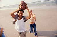 High angle view of a teenage couple playing football on the beach