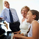 Grandmother and Granddaughter Playing Piano While Grandfather Listening
