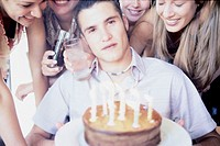 Young Women Surrounding Birthday Boy