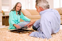 Mature couple playing backgammon in living room, smiling