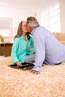 Mature couple kissing, sitting on carpet in living room