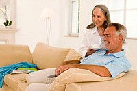 Mature couple sitting on sofa, watching TV, side view