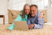 Mature couple lying on carpet, using laptop, smiling