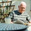 Senior man sitting at garden table reading, smiling