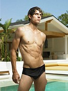 Young man in racing briefs standing beside pool, looking up