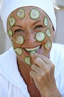 Senior woman with cucumber slices on face, close up, portrait