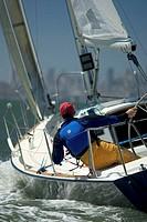 Man steering sailboat, rear view