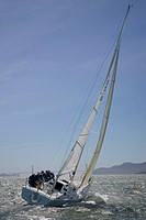 Crew sailing J105 sailboat in bay