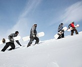 Four snowboarders walking up ski slope, side view
